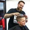 9-year-old Brayden Johns gets his hair cut by Kyle Ryan at Barlow's on June 28, 2018.<br /> Kelly Lafferty Gerber | Kokomo Tribune