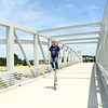 Local unicycle maker Tom Miller rides one of his unicycles across the Nickel Plate trail bridge after it was officially opened on Friday, June 29, 2018.<br /> Kelly Lafferty Gerber | Kokomo Tribune