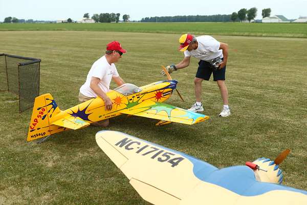 Barry Blanton, left, from Kokomo, holds the plane as Steve Eagle, from Wabash, flips the propeller to get the plane started as they fly with the Converse Flying Eagles R/C Club at the Converse Airport on Saturday, June 16, 2018.<br /> Kelly Lafferty Gerber | Kokomo Tribune