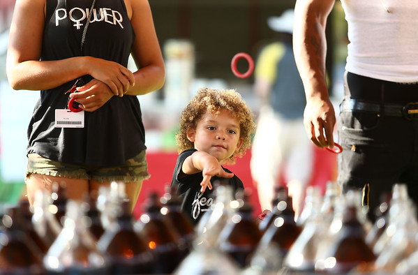 3-year-old Alekai Williams tries his hand at the ring-a-bottle game during the Haynes Apperson Festival on Thursday, June 28, 2018.<br /> Kelly Lafferty Gerber   Kokomo Tribune