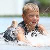 Dakotah Harris, 8, slides on the tarp at the water spray at Highland Park on Wednesday, June 27, 2018.<br /> Kelly Lafferty Gerber | Kokomo Tribune