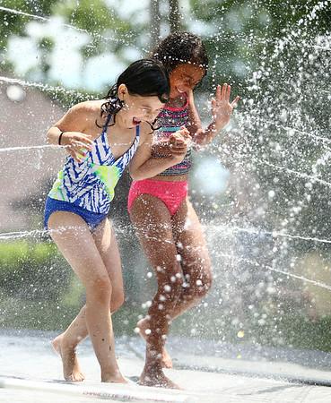 Sarah Hughes, 8, left, and Zaraiah Barbary, 9, hold hands as they walk through the water spray at Highland Park on Wednesday, June 27, 2018.<br /> Kelly Lafferty Gerber   Kokomo Tribune