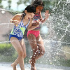 Sarah Hughes, 8, left, and Zaraiah Barbary, 9, hold hands as they walk through the water spray at Highland Park on Wednesday, June 27, 2018.<br /> Kelly Lafferty Gerber | Kokomo Tribune