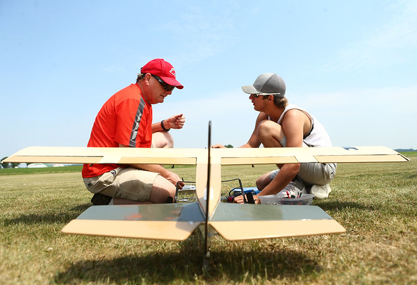 Larry Blanton, left, and Austin Morris work together to try and repair Blanton's radio control plane at the Converse Airport on Saturday. The Converse Flying Eagles R/C Club met at the Converse Airport for the annual egg drop competition.<br /> Kelly Lafferty Gerber   Kokomo Tribune