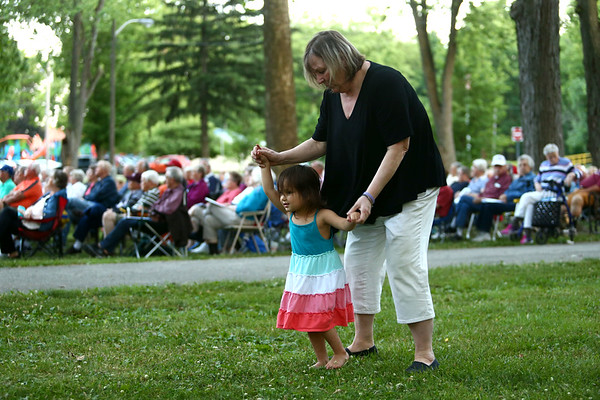 """Jane Williams dances with 3-year-old Elisha Parman as Kokomo Park Band plays selections from """"Grease"""" during their season opener at Highland Park on Wednesday, June 6, 2018.<br /> Kelly Lafferty Gerber   Kokomo Tribune"""