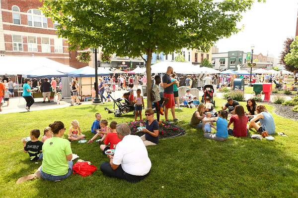 Strawberry Festival attendees take advantage of the shade in front of the Howard County Courthouse to eat their strawberry shortcake dessert in downtown Kokomo on Friday, June 1, 2018.<br /> Kelly Lafferty Gerber   Kokomo Tribune