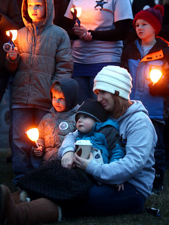 Kassie Koontz holds her son Noah as the two, surrounded by friends, family and supporters holding candles, remember Koontz's husband, Deputy Carl Koontz, 2 years after he was shot and killed. Deputy Carl Koontz's  memorial was at Albright Cemetery on Tuesday, March 20, 2018.<br /> Kelly Lafferty Gerber   Kokomo Tribune
