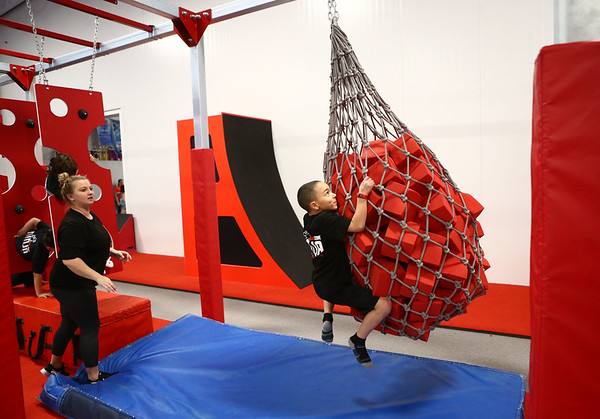 With the help of instructor Brittany Yard, 6-year-old Jayce Bryant swings along the zipline at Ninja Zone class course at Kokomo Flipsters on Tuesday, March 13, 2018.<br /> Kelly Lafferty Gerber   Kokomo Tribune
