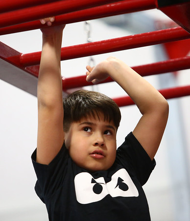 Daris Lopez, 8, eyes his next move on the hand-over-hand bars during the Ninja Zone class at Kokomo Flipsters on Tuesday, March 13, 2018.<br /> Kelly Lafferty Gerber   Kokomo Tribune