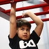 Daris Lopez, 8, eyes his next move on the hand-over-hand bars during the Ninja Zone class at Kokomo Flipsters on Tuesday, March 13, 2018.<br /> Kelly Lafferty Gerber | Kokomo Tribune