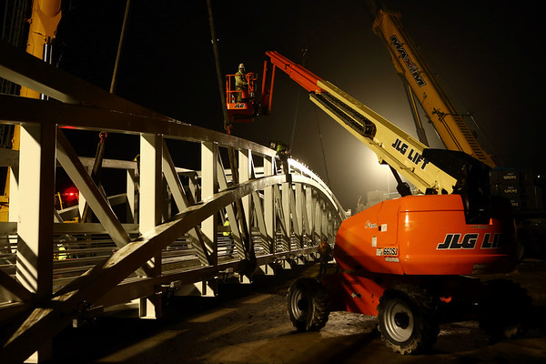 The construction crew works into the night on Wednesday, March 28, 2018, as they progress on the installation of the pedestrian bridge over 931. The bridge will connect the Nickel Plate trail to downtown Kokomo.<br /> Kelly Lafferty Gerber | Kokomo Tribune