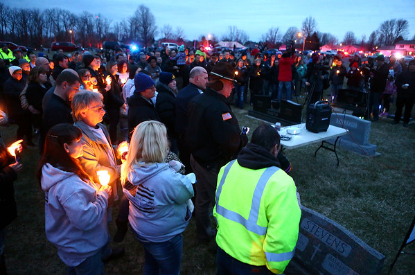 Attendees hold candles and watch a photo slideshow at Albright Cemetery on Tuesday, March 20, as they remember Deputy Carl Koontz, who was shot and killed two years ago.<br /> Kelly Lafferty Gerber | Kokomo Tribune