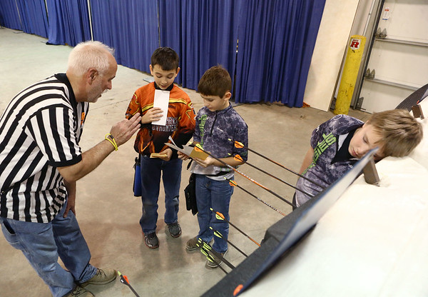 Line judge Frank Baker, left, helps young archers Zander Merritt and David Eaton with scoring as fellow archer Logan Burrell, right, takes a break during the 53rd annual Indiana Field Archery Association Indoor Tournament at the Kokomo Event Center on Saturday, March 3, 2018.<br /> Kelly Lafferty Gerber | Kokomo Tribune
