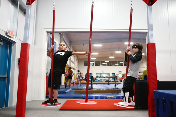 6-year-old Jayce Bryant, left, and 5-year-old Aaron Beaty balance themselves as they move through the swing poles during the Ninja Zone class at Kokomo Flipsters on Tuesday, March 13, 2018.<br /> Kelly Lafferty Gerber | Kokomo Tribune