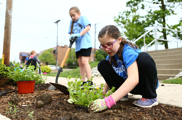 Emilie Leger, 9, plants flowers as Madison Smith, 9, digs a hole to plant more in the flower bed across from Central Middle School for Keep Kokomo Beautiful's annual planting day on Saturday morning, May 19, 2018.<br /> Kelly Lafferty Gerber   Kokomo Tribune