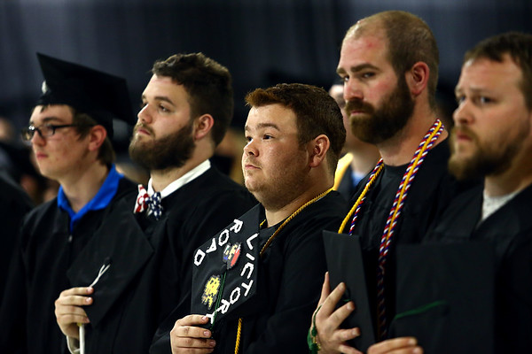 """James Robbins, center, holds his decorated """"Victory Road"""" graduation cap as he stands for the National Anthem during the Ivy Tech graduation on Friday, May 11, 2018.<br /> Kelly Lafferty Gerber 