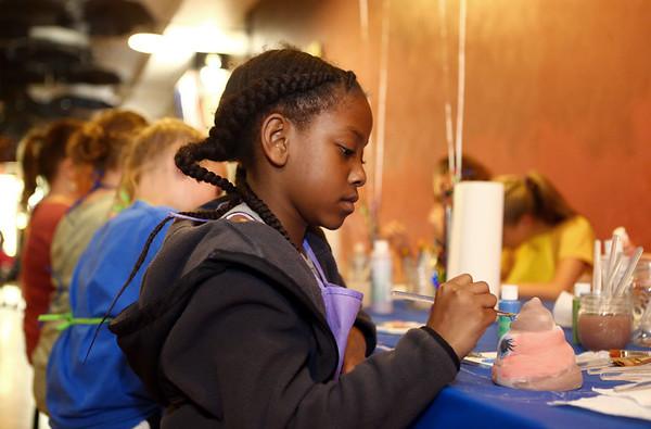 Koriyah Miller, 9, paints a poop emoji pottery piece at a friend's birthday party at Fired Arts Studio on May 19, 2018.<br /> Kelly Lafferty Gerber | Kokomo Tribune