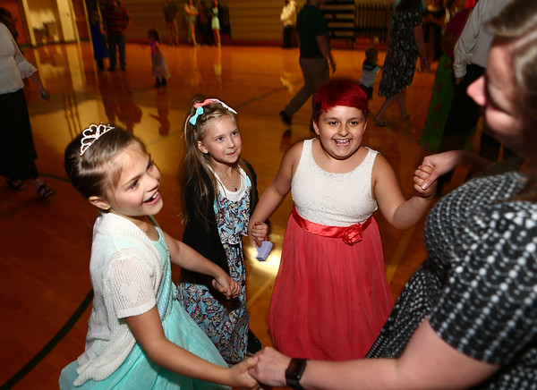 7-year-olds from left: Bralynn Gaddis, Franki Groves, and Serenity Torivo, dance with Bon Air Elementary assistant principal Lyndsi Smith during the family prom on Friday, May 18, 2018.<br /> Kelly Lafferty Gerber | Kokomo Tribune