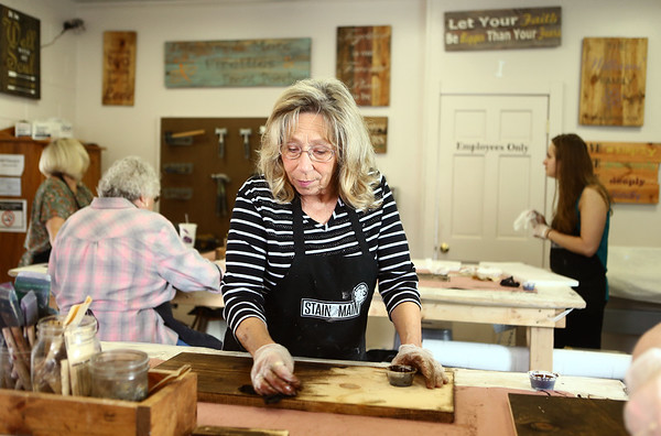 Judy McCain stains wood as she makes her own sign at Stain on Main on Saturday, May 12, 2018.<br /> Kelly Lafferty Gerber | Kokomo Tribune