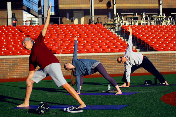 Nancy Salmon, Sarah Pate and Darrell Hollingworth participate in yoga at the stadium lead up by Conner Sanburn on May 23, 2018. <br /> Tim Bath   Kokomo Tribune