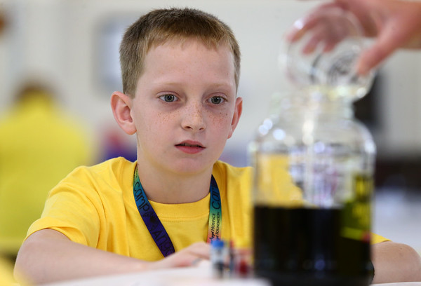 10-year-old Braden Wunderlich watches as the dark liquid becomes brighter during the Camp Angel day camp on Saturday, May 19, 2018. The kids talked about emotions they've felt after losing a loved one while they dropped food coloring into water, turning the water dark. Then they talked about the things that make them feel better as instructor Stephanie Guinn poured bleach into the jar, making the water clearer and brighter.<br /> Kelly Lafferty Gerber | Kokomo Tribune