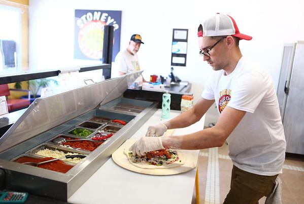 Stoney's Sourdough Pizza owner Adam Neher makes a pizza for customer Jim Roseberry on May 10, 2018.<br /> Kelly Lafferty Gerber | Kokomo Tribune