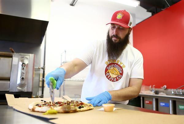 Jeff Watkins slices up a pizza for a customer at Stoney's Sourdough Pizza on May 10, 2018.<br /> Kelly Lafferty Gerber   Kokomo Tribune