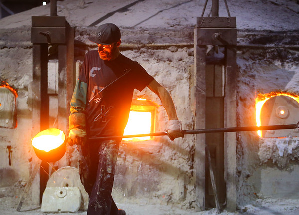 Head ladler Nick Downs carries hot glass to the mixing table at Kokomo Opalescent Glass on Friday, November 23, 2018.<br /> Kelly Lafferty Gerber   Kokomo Tribune