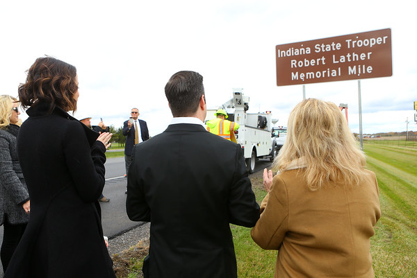 From left: Breanne Miller, Robert Lather III, and Teresa Bodnyk applaud after the Memorial Mile marker for their dad and Bodnyk's husband, Trooper Robert Lather II, is unveiled during a dedication ceremony on Friday, November 2, 2018. Trooper Lather, who was killed in 1982, was the 28th Indiana State Police officer to die in the line of duty.<br /> Kelly Lafferty Gerber | Kokomo Tribune