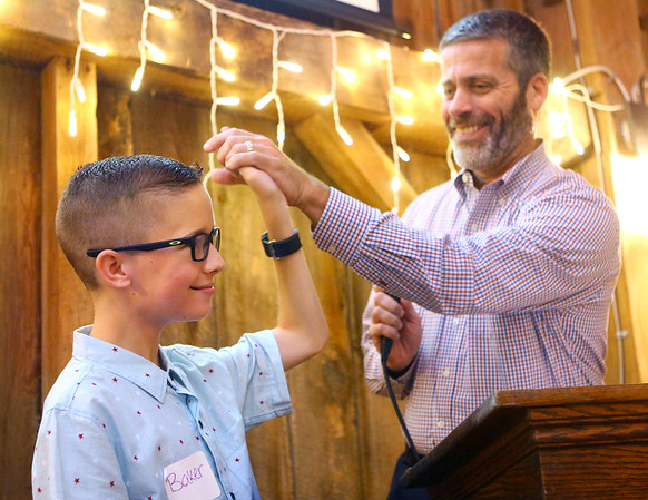 Baker gets a high-five from Howard County commissioner Paul Wyman after Baker successfully auctioned off items during an event at the Legacy Barn on September 13. Baker, who saw his first auction two years ago, wants to be an auctioneer when he grows up and is already achieving his dream.<br /> Kelly Lafferty Gerber | Kokomo Tribune