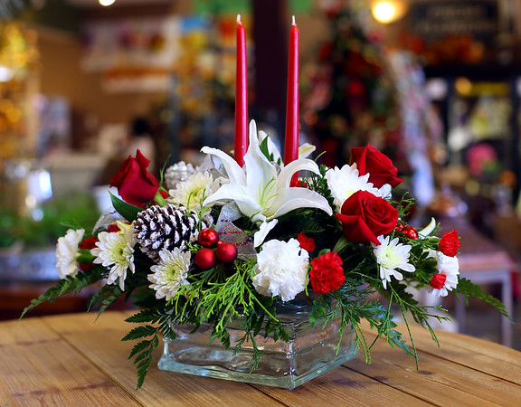Traditional 2 candle centerpiece with red roses and white flowers accents, wintergreens and pine cones on Oct. 16, 2018. <br /> Tim Bath | Kokomo Tribune