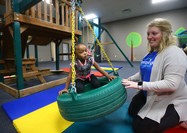 Molly Benziger, right, registered behavior technician, gently pushes 3-year-old Keyonna Belton in the tire swing at Hopebridge Autism Therapy Center in Kokomo on October 18, 2018.<br /> Kelly Lafferty Gerber | Kokomo Tribune