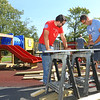 Anthony Larson, left, from Lowes, and Chad Strader, from Grissom, cut pieces of wood as they work together on improving Taylor Elementary's playground equipment on Friday, September 28, 2018.<br /> Kelly Lafferty Gerber | Kokomo Tribune
