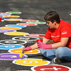 Molly Duranto from Lowes paints an alphabet caterpillar on the black top at Taylor Elemntary's playground on Friday, September 28, 2018.<br /> Kelly Lafferty Gerber | Kokomo Tribune