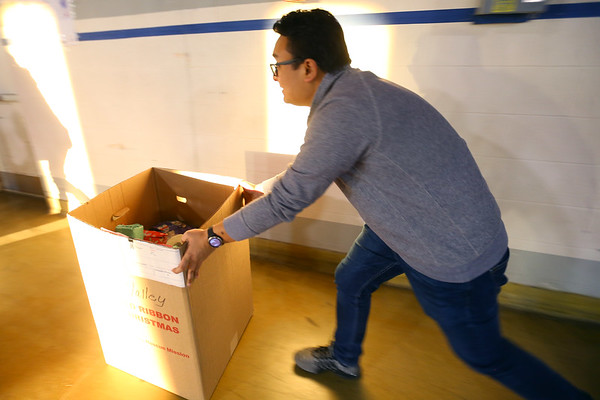 Ivaan Shrestha pushes a box of gifts toward the door to be loaded in vehicles at GM to be delivered during the Rescue Mission Red Ribbon Christmas event on December 19, 2019.<br /> Tim Bath | Kokomo Tribune