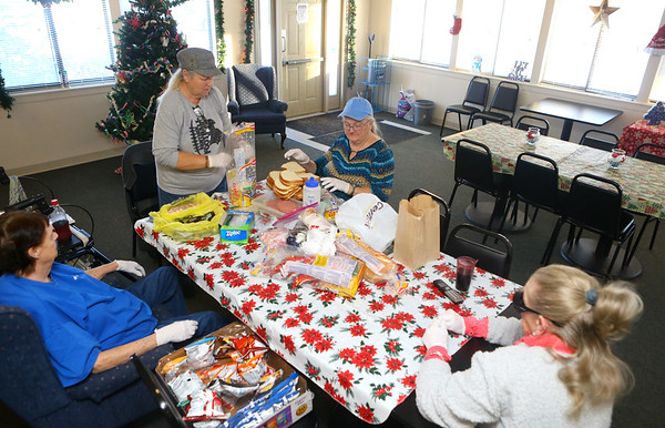 From left: Edith Clemons, Kay French, Linda Butler, and Ms. Cricket work together to put together sandwiches and sack lunches on December 19, 2019, to give away at the trolley station in downtown Kokomo.<br /> Kelly Lafferty Gerber | Kokomo Tribune