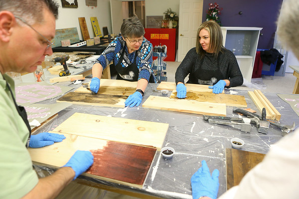 Angie Love, left, and Trisha Hand chat as they stain their boards during a workshop at Stain on Main, located at 401 Rainbow Dr., on Wednesday, December 18, 2019.<br /> Kelly Lafferty Gerber | Kokomo Tribune
