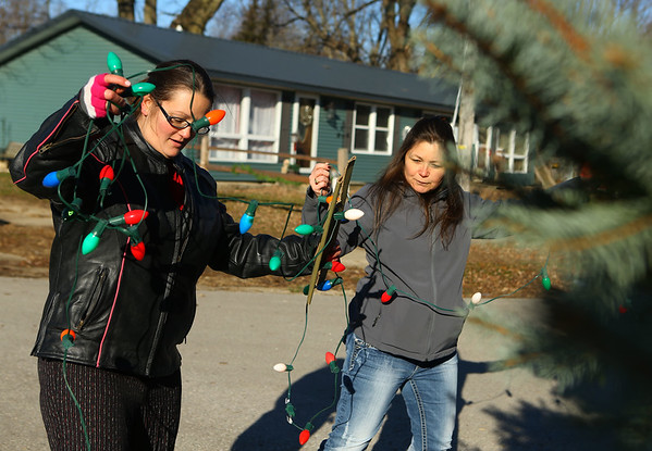 Amanda Cook, left, and Chastity Roark manuever around the tree as they work together to hang lights on Saturday, December 7, 2019, continuing an 80-year tradition of putting up a Christmas tree in the middle of town, at the intersection of Elm and and Fulton streets.<br /> Kelly Lafferty Gerber | Kokomo Tribune