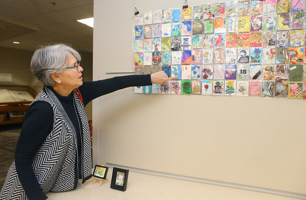 Rebecca Rayls, organizer of the artist trading card project, points out particular ones as she talks about the project on display at the Kokomo-Howard County Public Library on December 17, 2019. The exhibit will be on display until the end of January.<br /> Kelly Lafferty Gerber | Kokomo Tribune