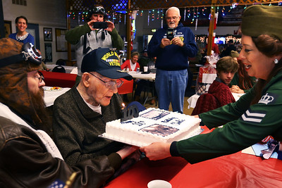 Granddaughter JoAnna Daily holds up the cake for WW II veteran Charlie Ormsby to blow out the candles at his 100th birthday party at the VFW 1152 hall on December 28, 2019.  Tim Bath | Kokomo Tribune