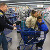 Indiana State Police trooper Kyle Miller pushes siblings Azalin Barber, 11, an Anthony Barber, 9, in the cart as they shop during Cops4Kidz at Meijer on Saturday, December 14, 2019.<br /> Kelly Lafferty Gerber | Kokomo Tribune