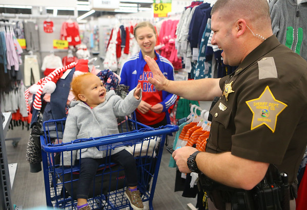 Sgt. Justin Markley from the Howard County Sheriff Department highfives 17-month-old La'Reyah Tamayo as he makes her laugh while Kokomo High School varsity cheerleader freshman Sophia Justice looks on during Cops4Kidz at Meijer on Saturday, December 14, 2019.<br /> Kelly Lafferty Gerber | Kokomo Tribune