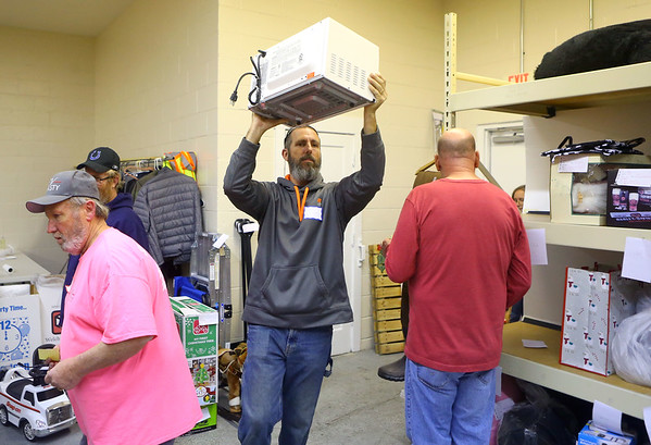 Shad Smith carries a microwave to the highest bidder during the final hours of the 2019 We Care telethon on Sunday, December 8, 2019.<br /> Kelly Lafferty Gerber | Kokomo Tribune