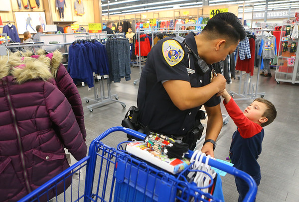 4-year-old Alaki Duke asks Kokomo Police Department officer Alejandro Ramirez about the patches on his uniform during Cops4Kidz at Meijer on Saturday, December 14, 2019.<br /> Kelly Lafferty Gerber | Kokomo Tribune