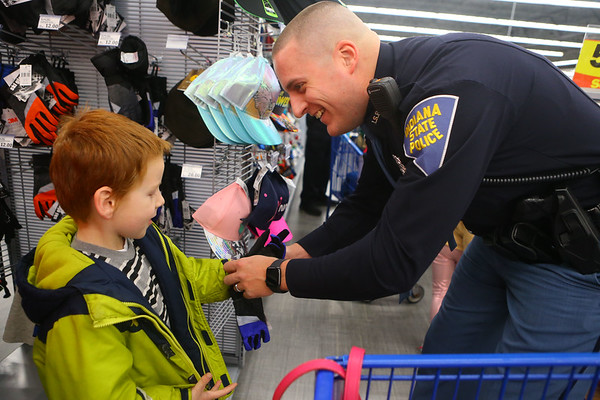 Indiana State Police trooper Chad Babbs puts a glove on 5-year-old Silas Long as they shop together during Cops4Kidz at Meijer on Saturday, December 14, 2019.<br /> Kelly Lafferty Gerber   Kokomo Tribune