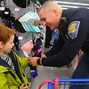 Indiana State Police trooper Chad Babbs puts a glove on 5-year-old Silas Long as they shop together during Cops4Kidz at Meijer on Saturday, December 14, 2019.<br /> Kelly Lafferty Gerber | Kokomo Tribune