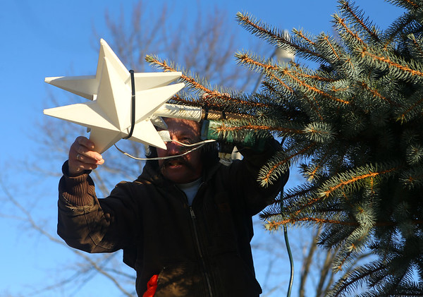 Dave Hamby affixes the star to the top of the tree before it's raised and secured in the middle of Miami, at the intersection of Elm and and Fulton streets on Saturday, December 7, 2019.<br /> Kelly Lafferty Gerber   Kokomo Tribune