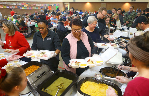 Volunteer Anita Smith, center, helps out attendees by filling and running trays of food during the 24th annual Favors Christmas dinner on Wednesday, December 25, 2019.<br /> Kelly Lafferty Gerber | Kokomo Tribune