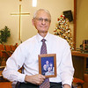 Pastor Jeff Russell holds a photo of his four children inside New Beginnings Christian Fellowship's sanctuary on December 4, 2019. Russell's two sons, Jeffry and Rick, have both passed away. The church is hosting a candlelight vigil at 7 p.m. this Sunday night for families who have lost a loved one, particularly a child.<br /> Kelly Lafferty Gerber | Kokomo Tribune