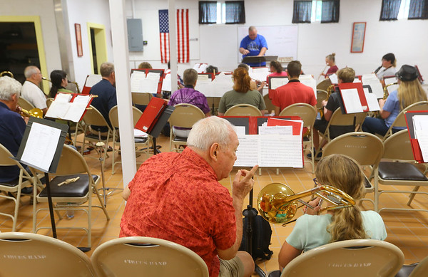 Tom Gustin, left, gives 11-year-old Macy Buck some pointers with the trombone during rehearsal on July 3, 2019. Gustin has been part of the Peru Circus band since its first year, 60 years ago.<br /> Kelly Lafferty Gerber | Kokomo Tribune